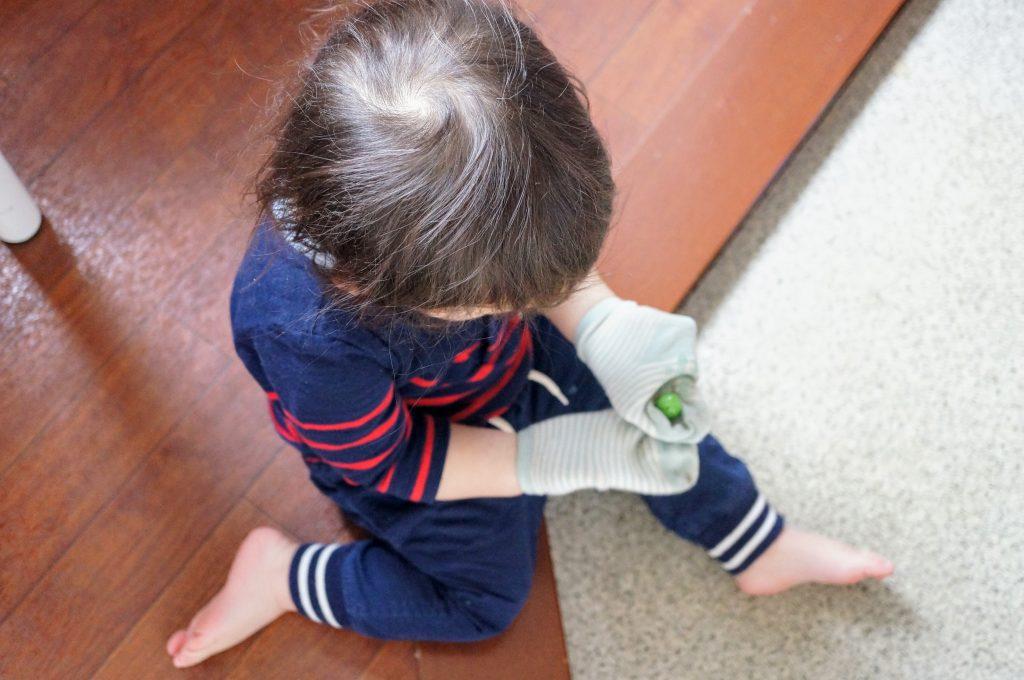 靴下を手にはめて、ビー玉と戯れる息子